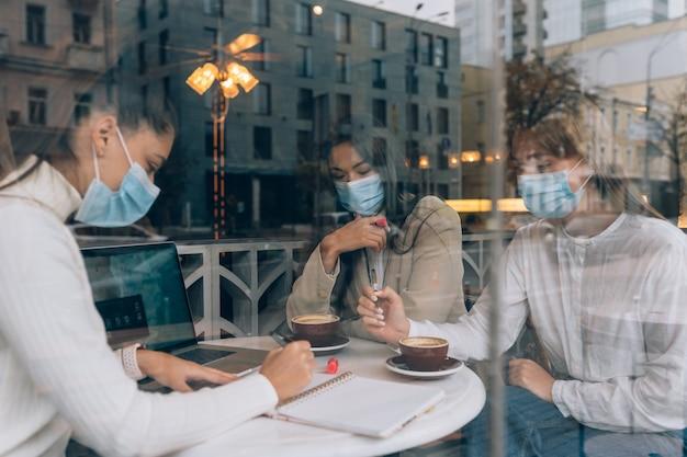 Vrienden die meisjes in een café hebben ontmoet, dragen medische beschermende maskers