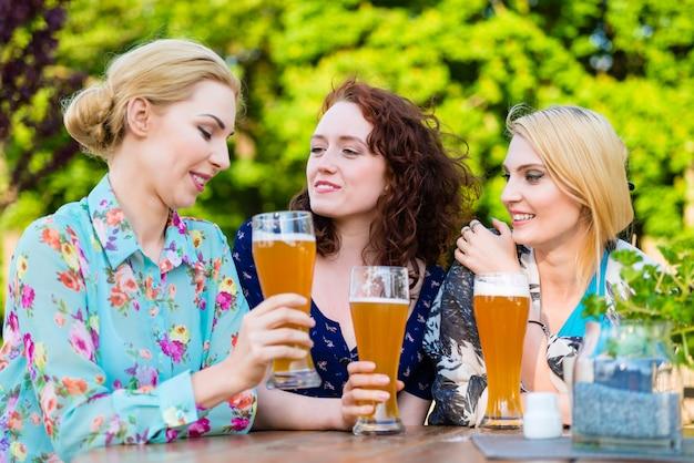 Vrienden die met bier in tuinbar roosteren