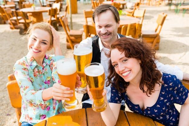 Vrienden die met bier in tuinrestaurant roosteren