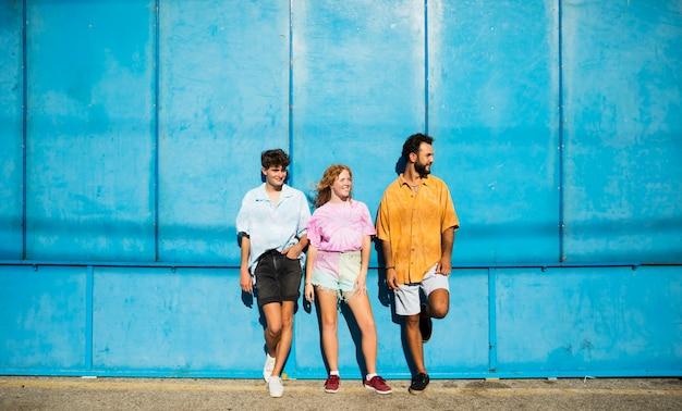 Vrienden die met blauwe muur stellen