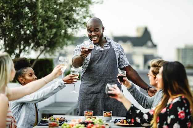 Vrienden die met de chef-kok op een de zomerpartij roosteren