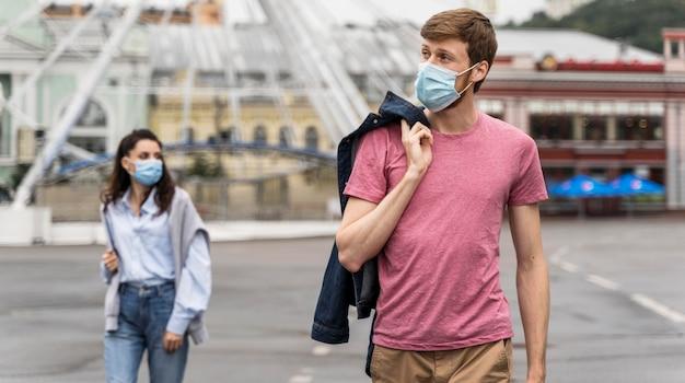 Vrienden die met gezichtsmaskers wegkijken