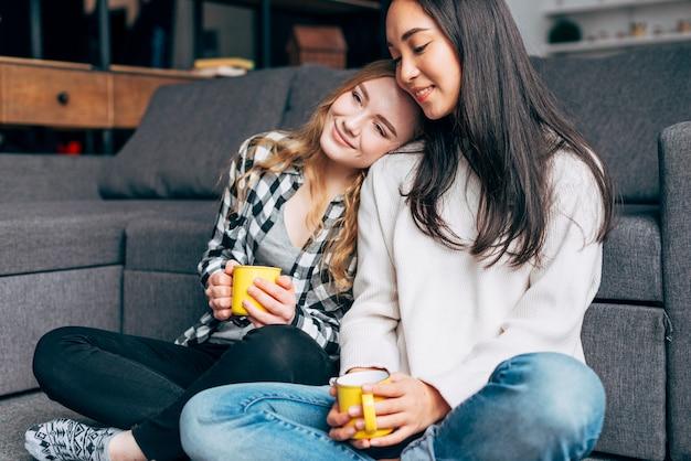 Vrienden die met mokken thee rusten