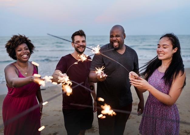 Vrienden die met sterretjes bij het strand vieren