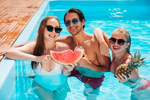 Vrienden die met watermeloen en ananas stellen