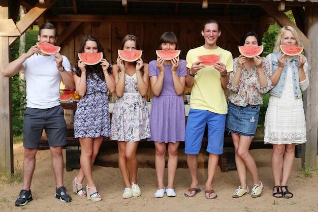 Vrienden die met watermeloenplakken stellen