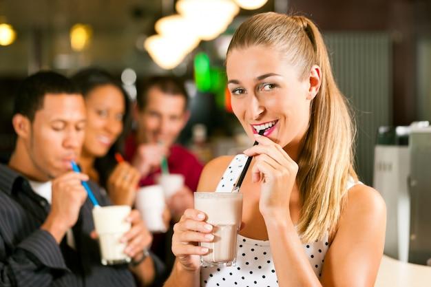 Vrienden die milkshakes in een bar drinken
