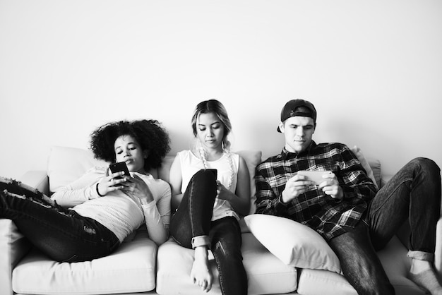 Vrienden die mobiele telefoons gebruiken op de bank