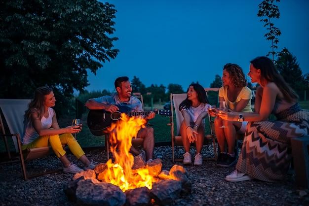 Vrienden die muziek spelen en van vuur in aard genieten.