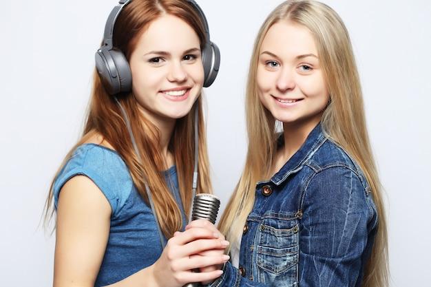 Vrienden die oortelefoons gebruiken en een microfoon houden