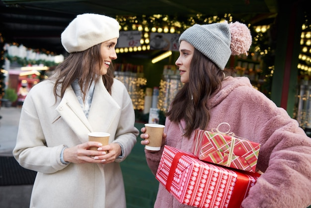 Vrienden die op de kerstmarkt cadeautjes dragen en glühwein drinken