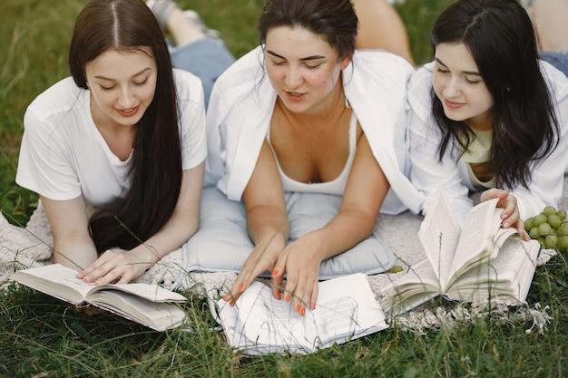 Vrienden die op een gras zitten. meisjes op een deken. vrouw in een wit overhemd.