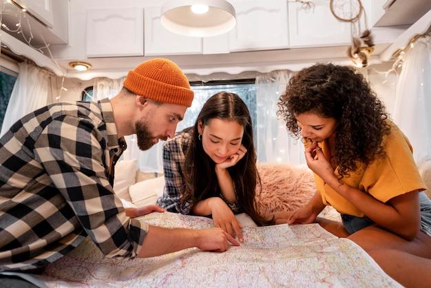 Vrienden die op een kaart in het busje kijken