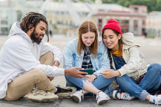 Vrienden die op floorand mobiel controleren zitten