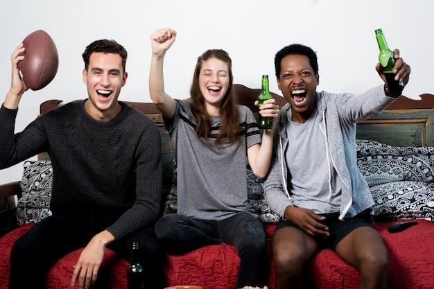 Vrienden die op sofa watching sport together zitten