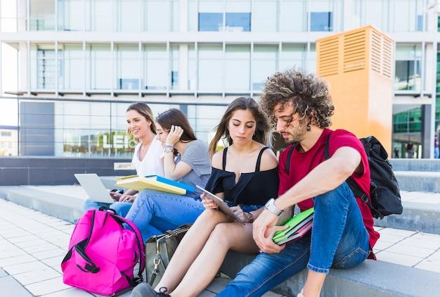 Vrienden die op stadsstraat bestuderen