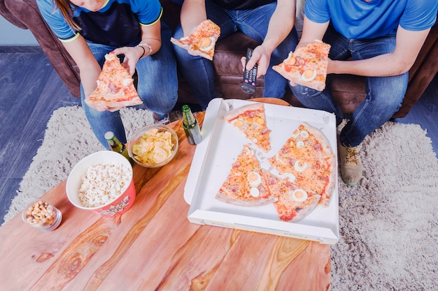 Vrienden die pizza eten en voetbal bekijken
