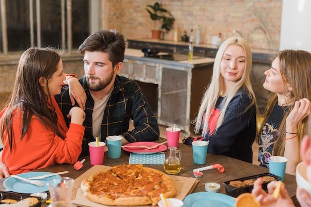 Vrienden die pizza eten op een feestje