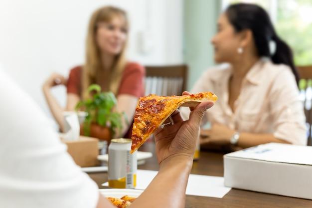 Vrienden die pizza eten tijdens vergadering samen bij pizzeria.