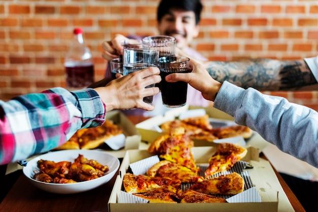 Vrienden die pizza samen thuis eten