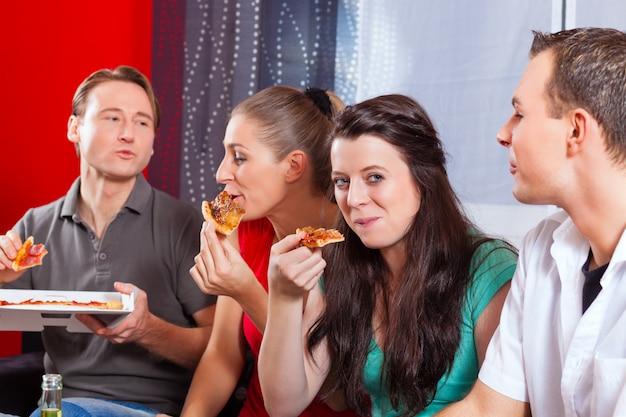 Vrienden die pizza thuis eten