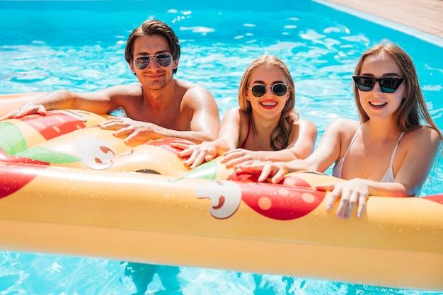 Vrienden die pizza zwemmende vlotter houden