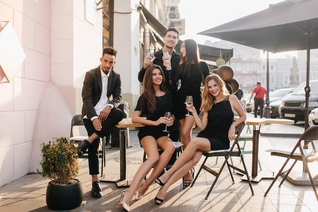 Vrienden die plezier hebben en buiten champagne drinken