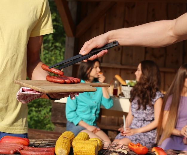 Vrienden die plezier hebben en voedsel grillen in het kamp