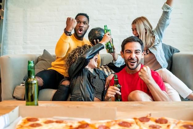 Vrienden die plezier hebben terwijl ze samen naar een wedstrijd kijken.