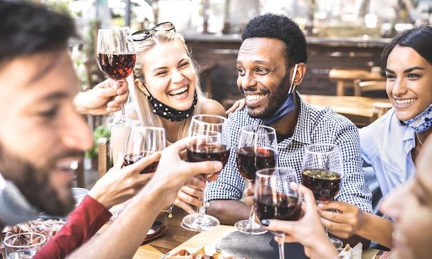 Vrienden die rode wijn roosteren bij restaurantbar die open gezichtsmasker dragen