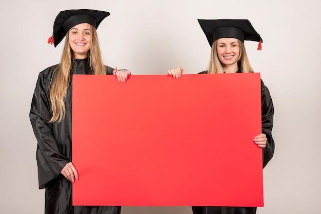 Vrienden die rood aanplakbiljet houden bij graduatie