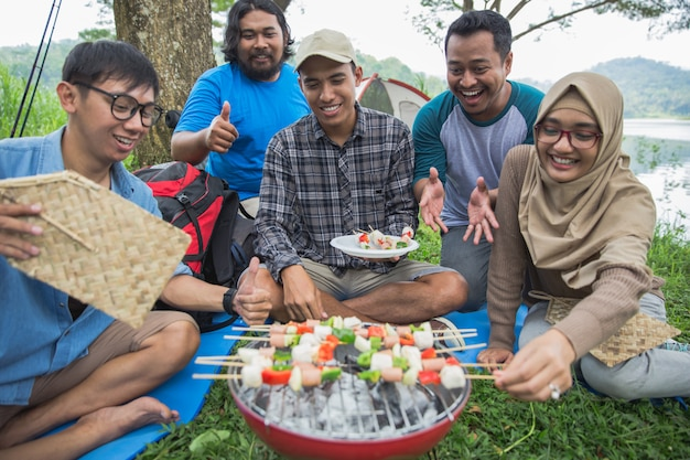 Vrienden die samen in openlucht een barbecue maken