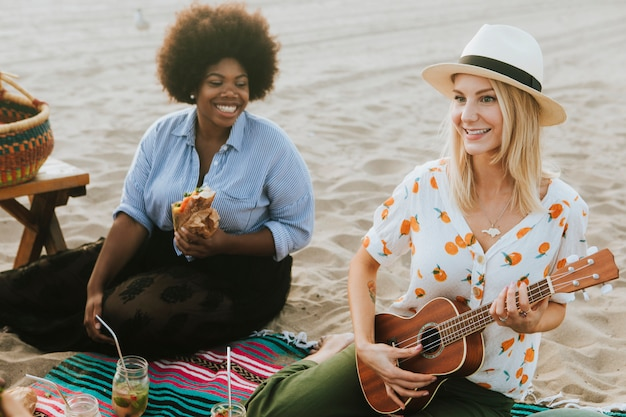 Vrienden die samen op een strandpicknick zingen