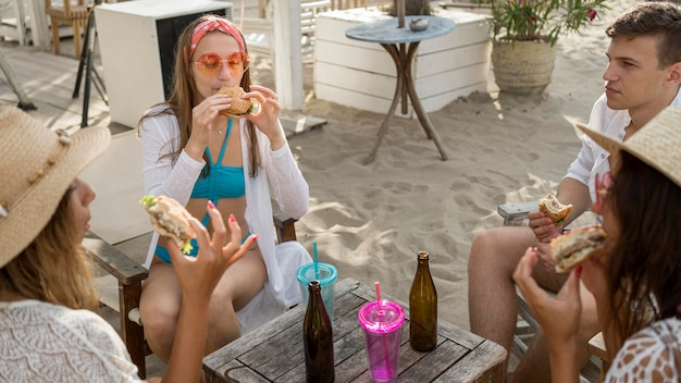 Vrienden die samen op het strand hamburgers eten