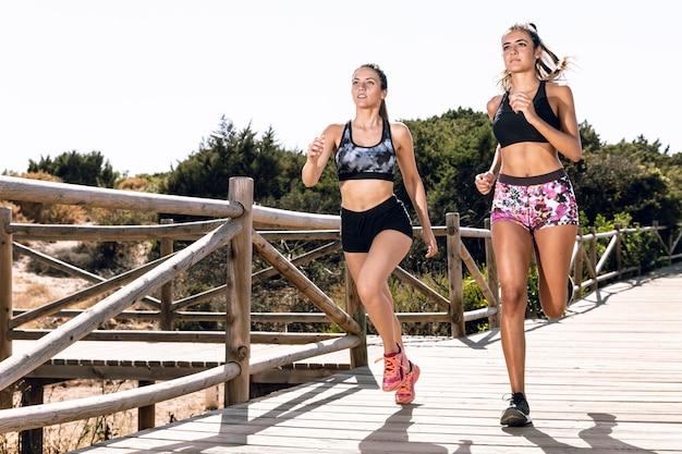 Vrienden die samen op pijler joggen