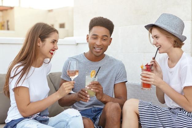 Vrienden die samen witte wijn en verse cocktails drinken terwijl ze iets bespreken