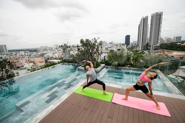 Vrienden die samen yoga beoefenen bij het zwembad
