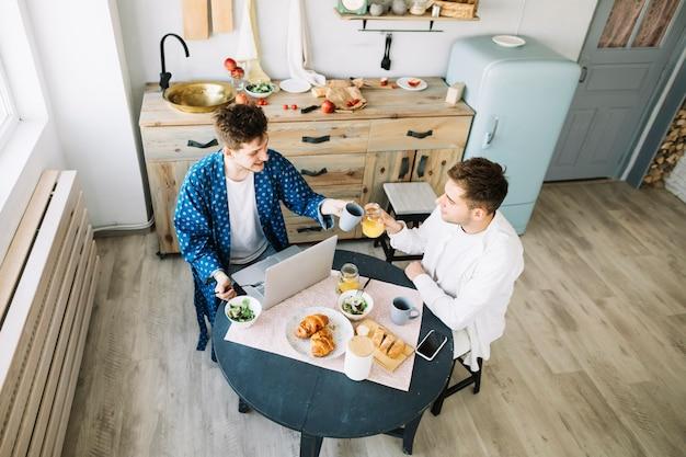 Vrienden die sap en koffiekop in de tijd op keuken roosteren