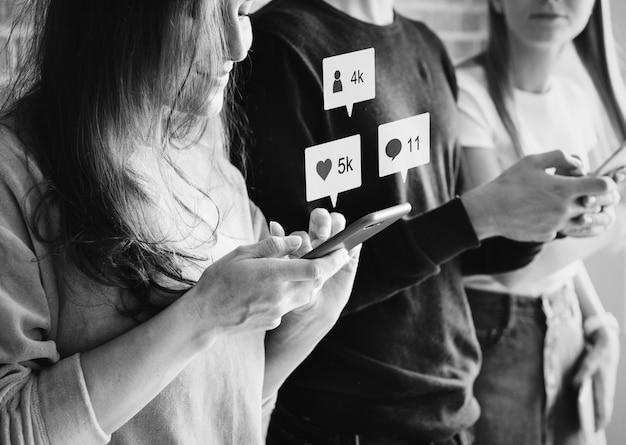 Vrienden die smartphones samen in openlucht gebruiken