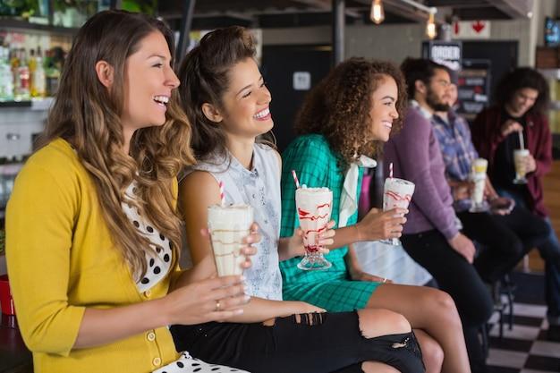 Vrienden die smoothie drinken bij restaurant