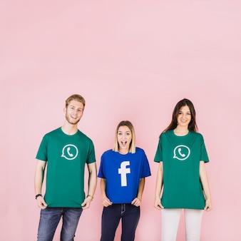 Vrienden die sociale media pictogramt-shirt op roze achtergrond dragen
