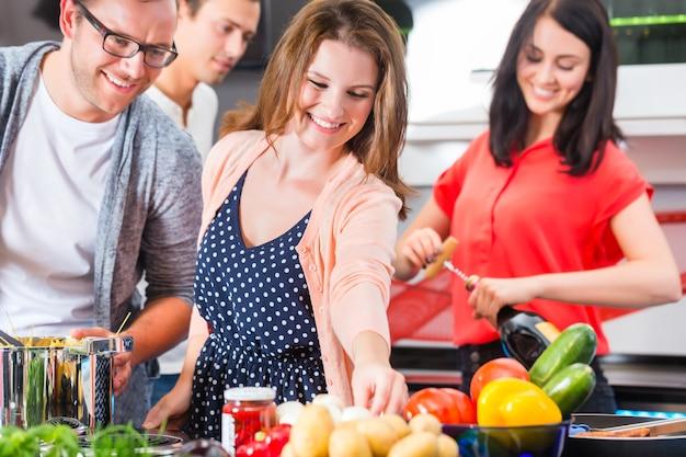 Vrienden die spaghetti en vlees in binnenlandse keuken koken