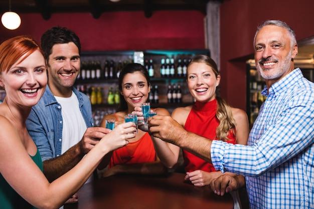 Vrienden die tequilaglazen in nachtclub roosteren