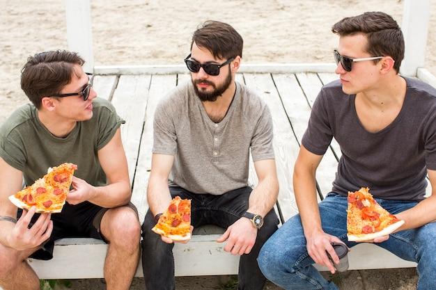 Vrienden die terwijl het zitten met pizza op strand converseren