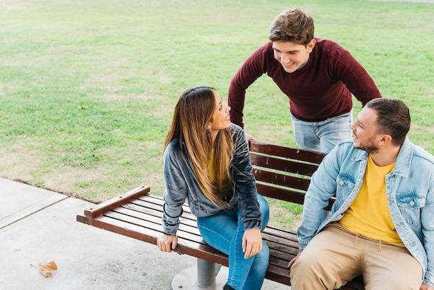 Vrienden die van dag in parkzitting genieten op bank