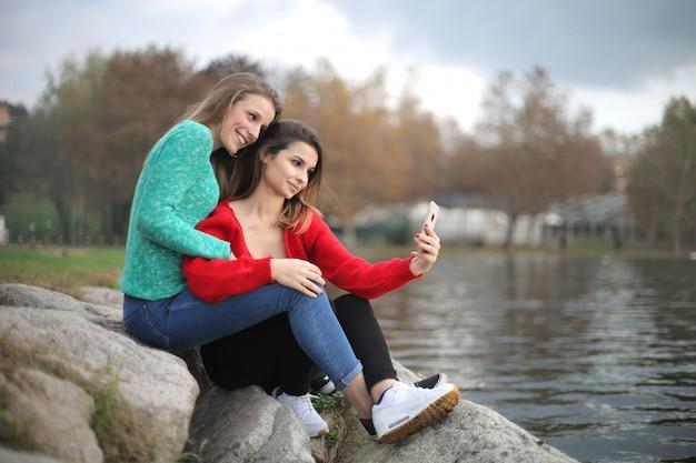 Vrienden die van een dag genieten bij het meer, die een foto nemen