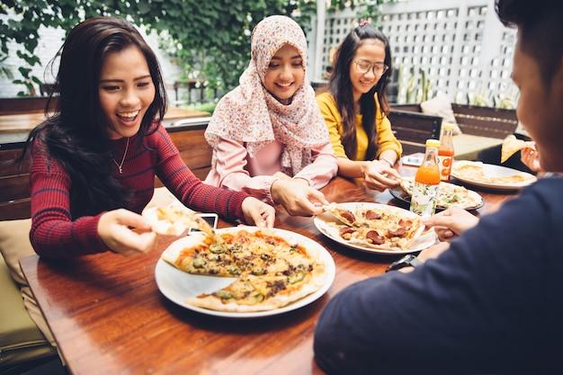 Vrienden die van maaltijd in openluchtrestaurant genieten