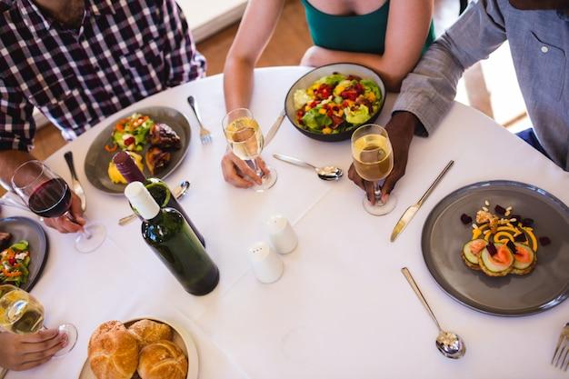 Vrienden die van voedsel en wijn genieten bij lijst in restaurant