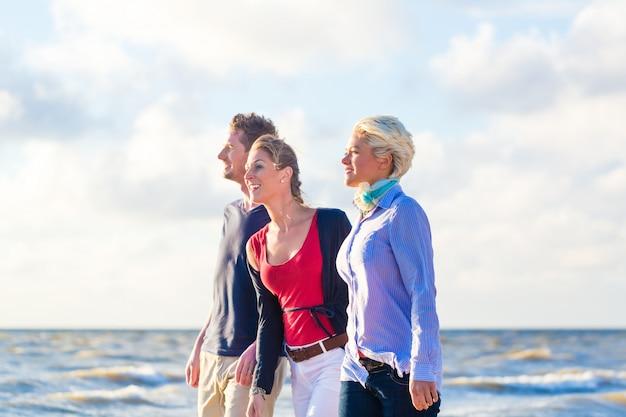 Vrienden die van zonsondergang genieten bij oceaanstrand