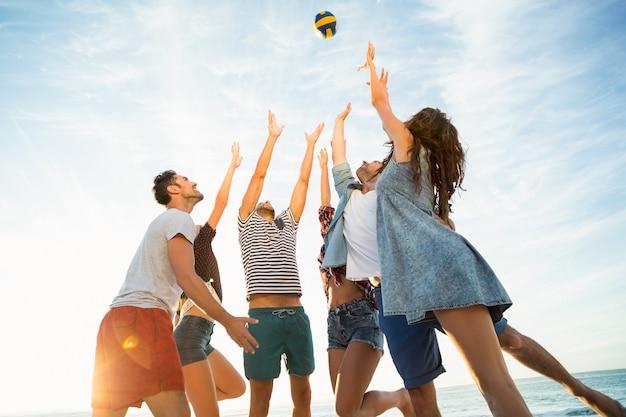 Vrienden die volleybal proberen te vangen